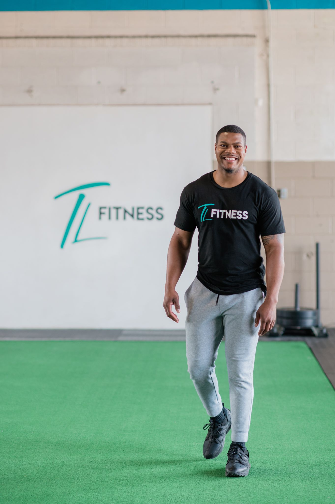 """A man, Torrey Lowe, smiles and walks towards the camera. He is in a gym with """"TL Fitness"""" written on the wall."""