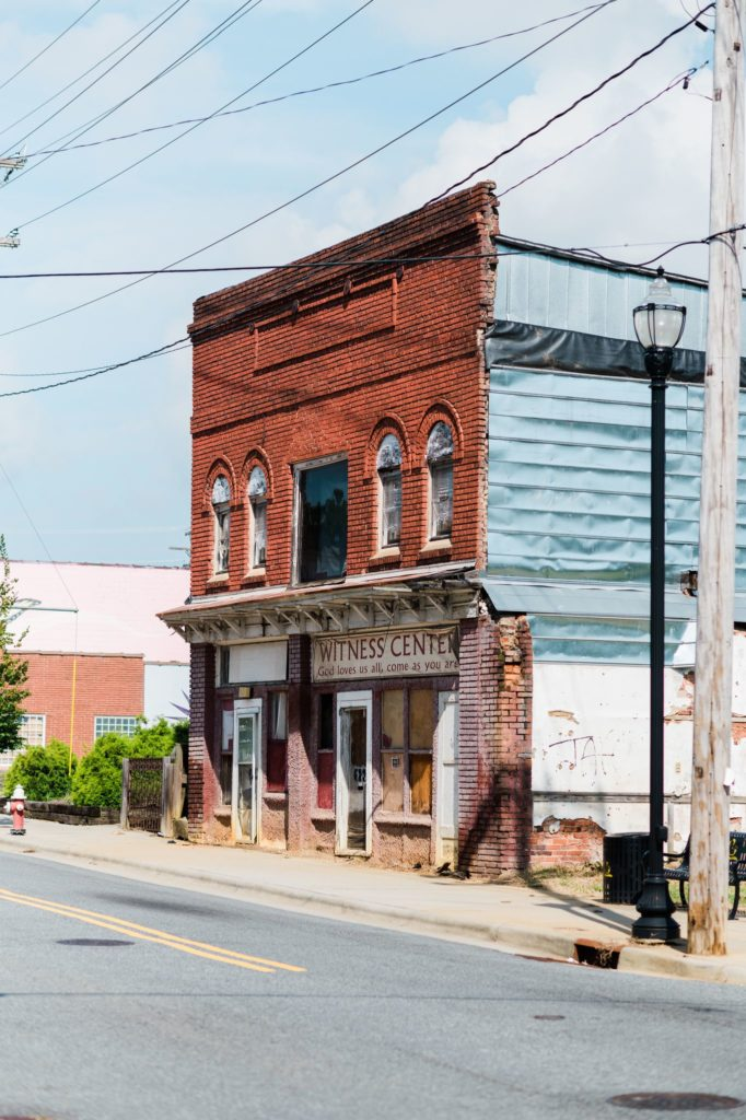 """A brick building stands on Washington Street in High Point with the words """"Witness Center"""" on the front."""