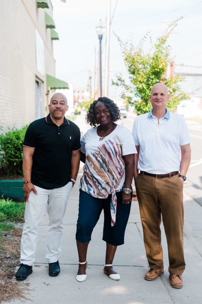 Bryon Stricklin, Telissa Ward, and Patrick Harman stand side by side on the sidewalk.