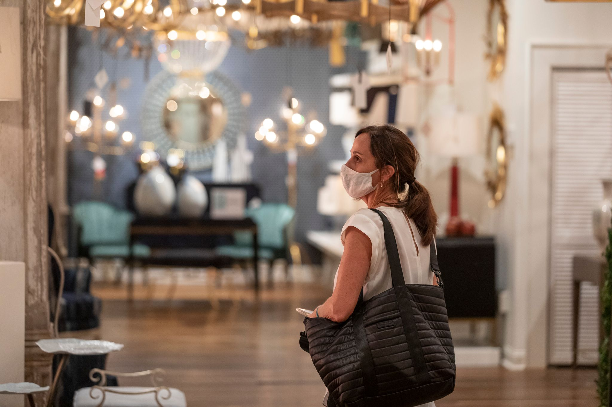 A woman stands in a furniture showroom looking at various objects. She is carrying a large bag and wearing a cloth mask.