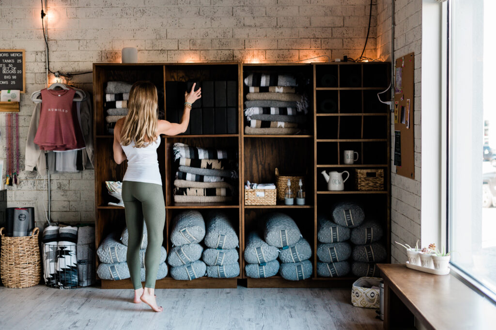 Stacey Field stacks materials in a shelves at Humbled Warriors Yoga.