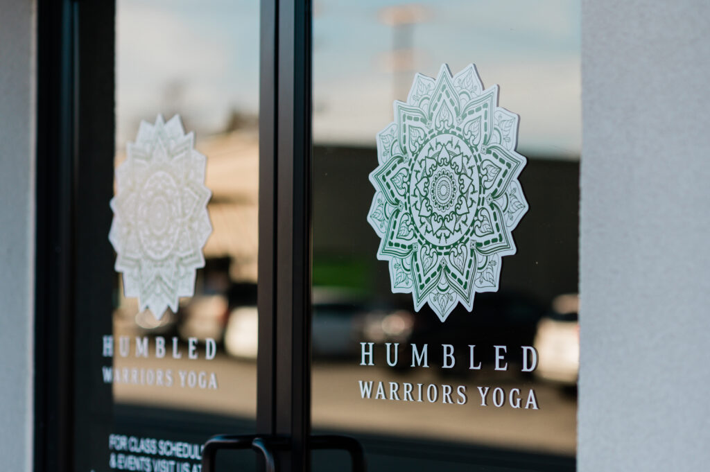 Glass door in the front of Humbled Warriors Yoga with a logo.