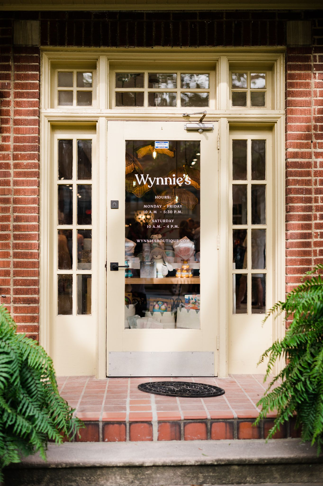 "Storefront of a brick building with glass door that says ""Wynnie's."""