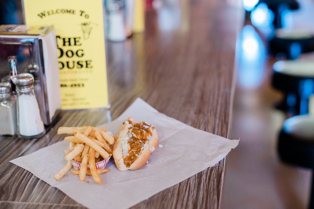 "A counter at a restaurant with a hotdog with chili and french fries lies on a piece of butcher paper in front of a yellow menu that says ""The Dog House."""