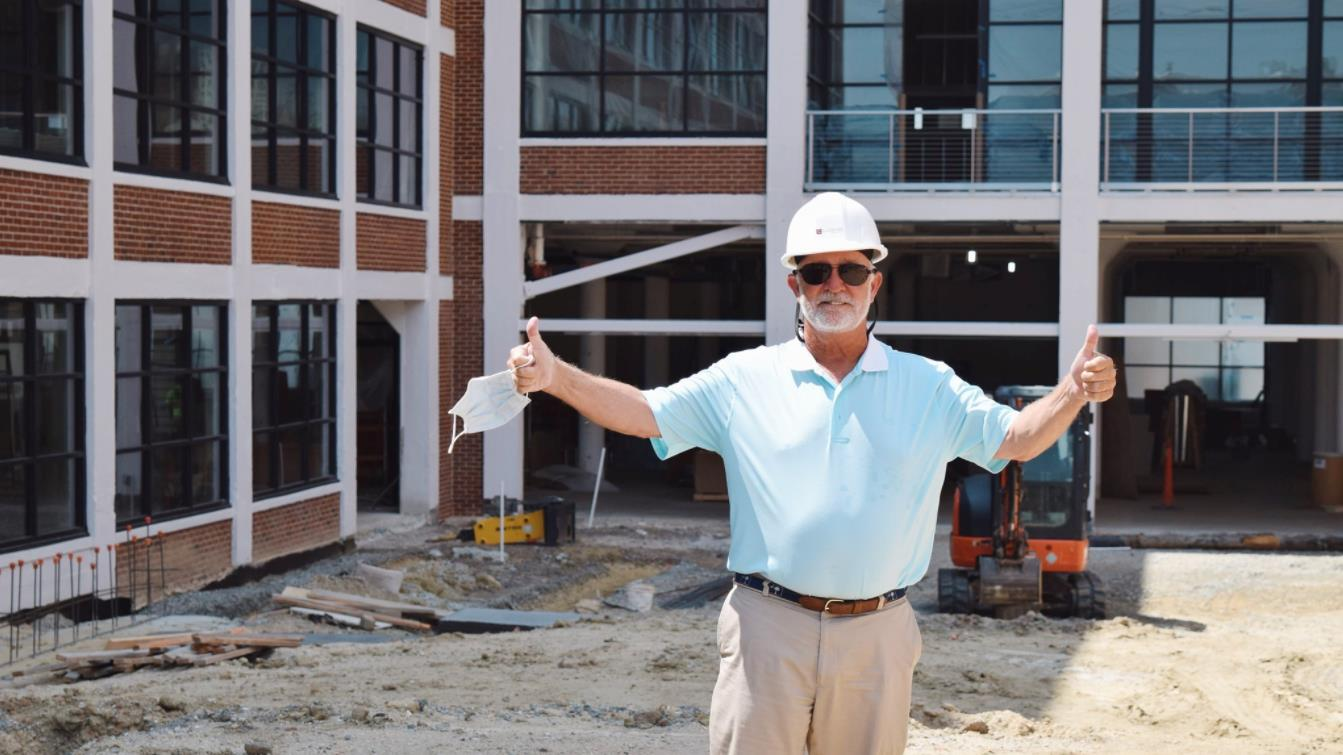 David Congdon stands in a hard hat, giving two thumbs up in front of Congdon Yards.