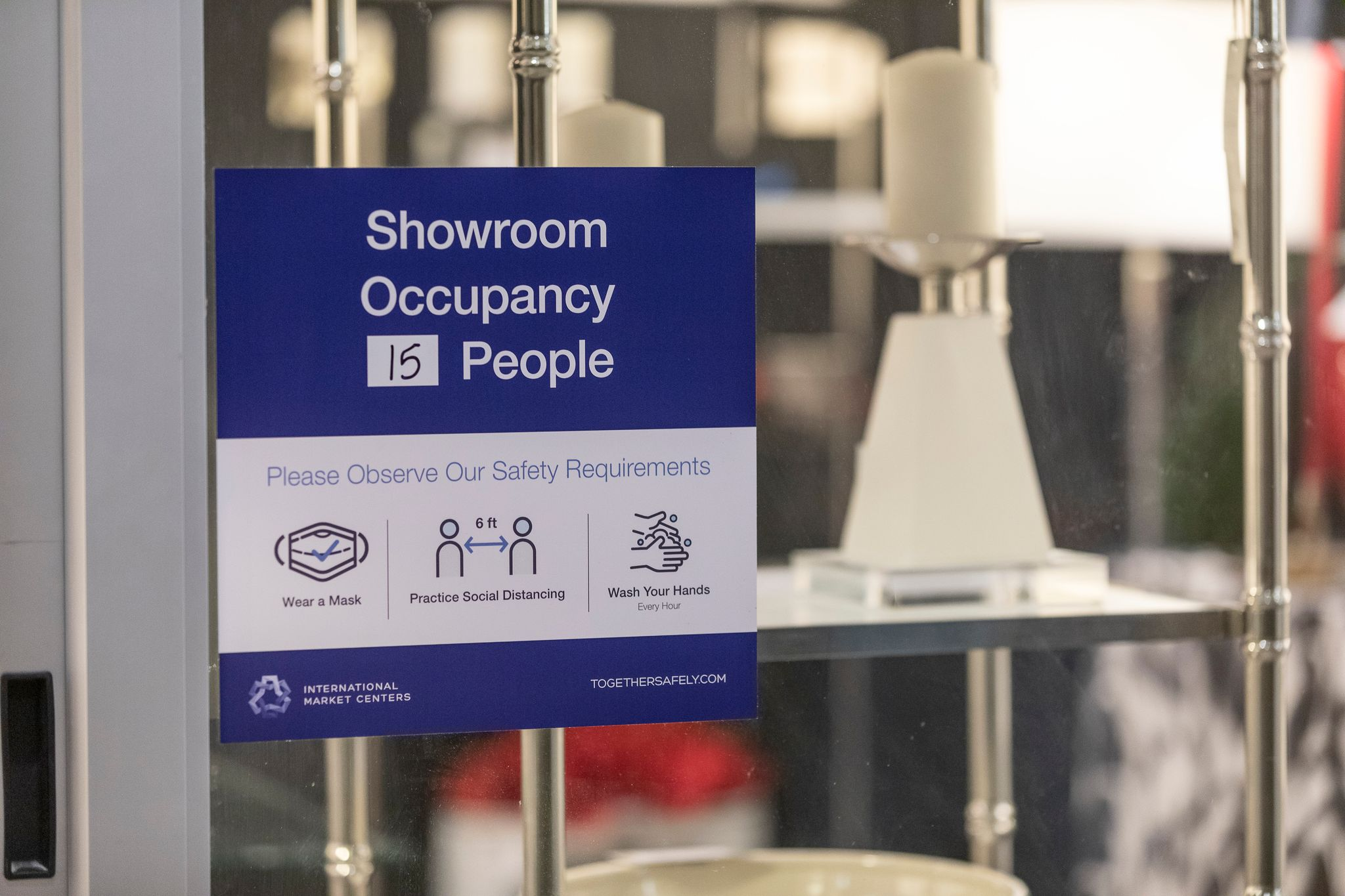 "A sign that says ""Showroom Occupancy 15 People"" hangs on a glass door."