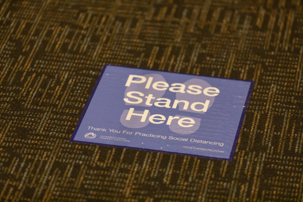 """On gray carpet lays a sign with two footprint outlines that says, """"Please Stand Here."""""""