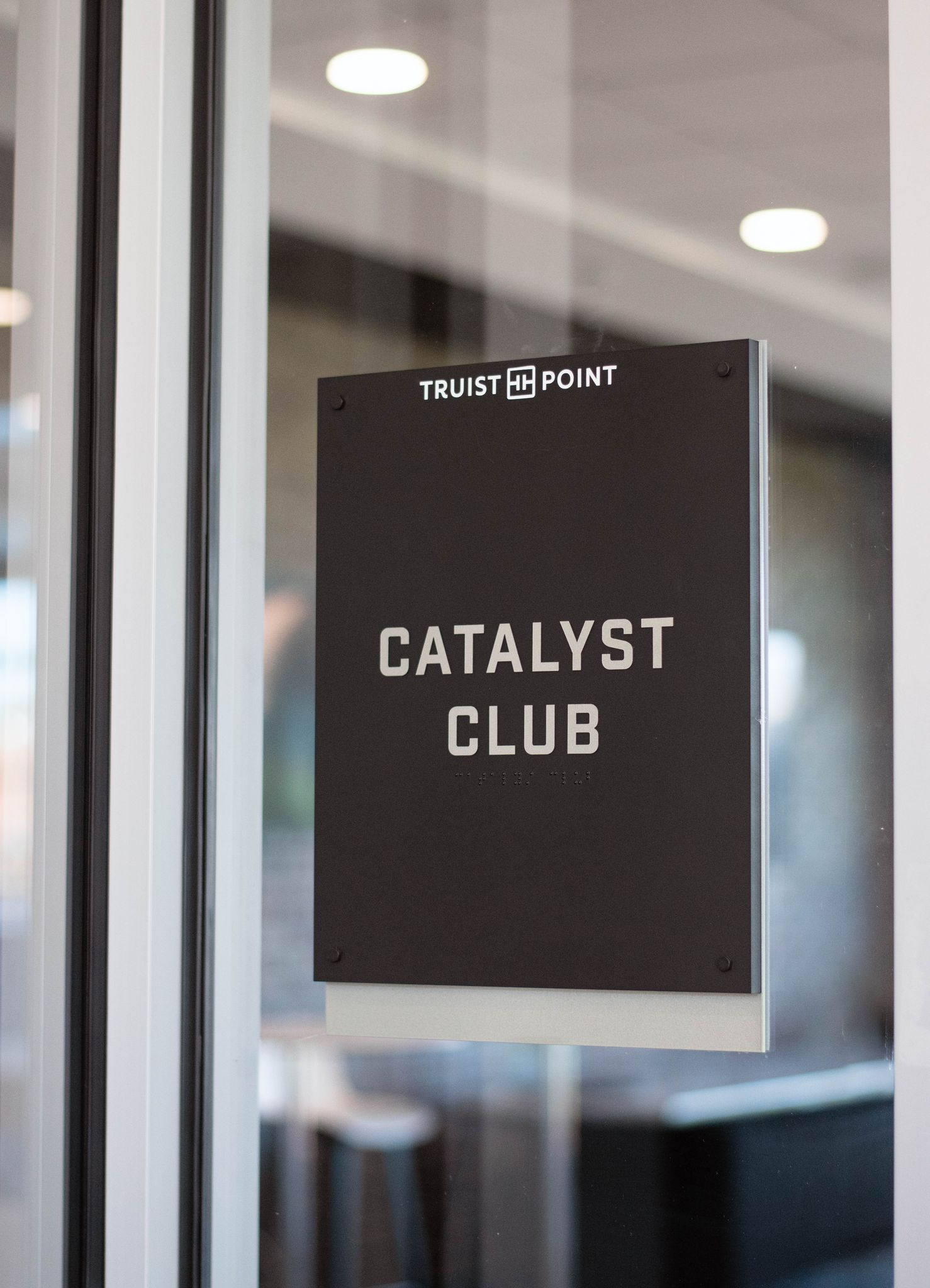 "A gray sign on a glass door that reads ""Catalyst Club."""