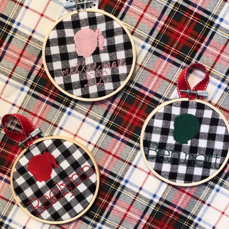 A plaid print table cloth with small embroidered hoops of children's silhouettes on buffalo plaid from Dwell and Wander Goods.