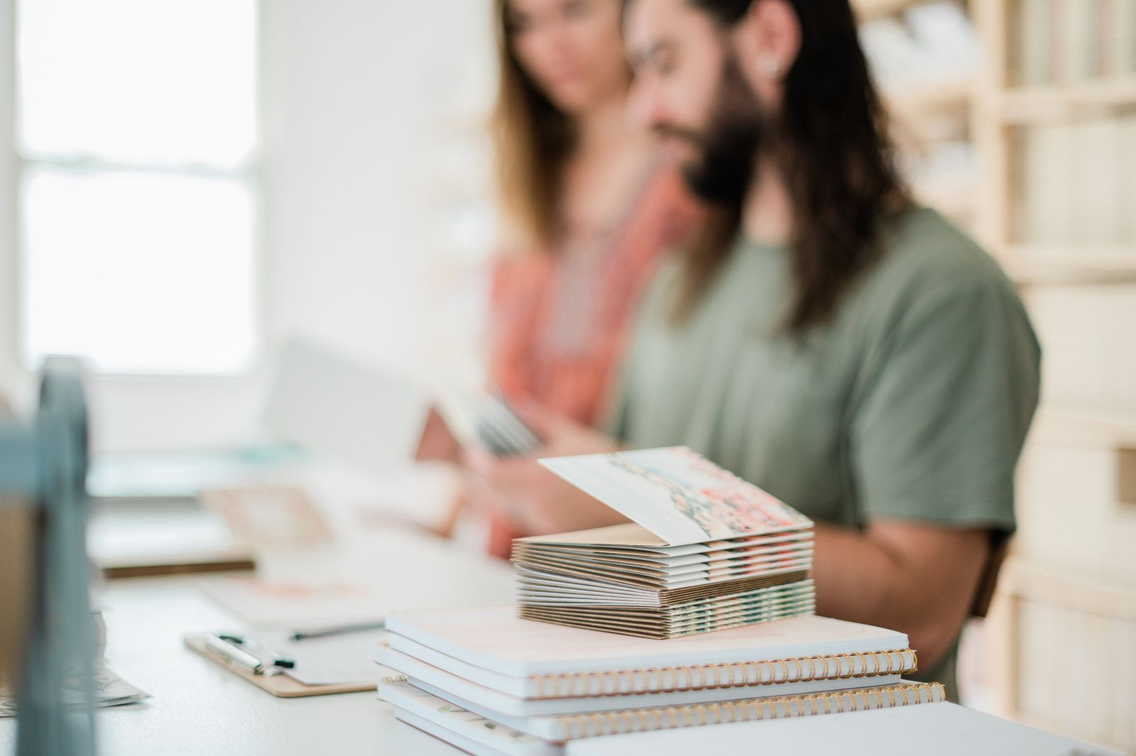 Justin and Taylor, owners of Pen + Pillar work at a table behind a stack of notebooks.