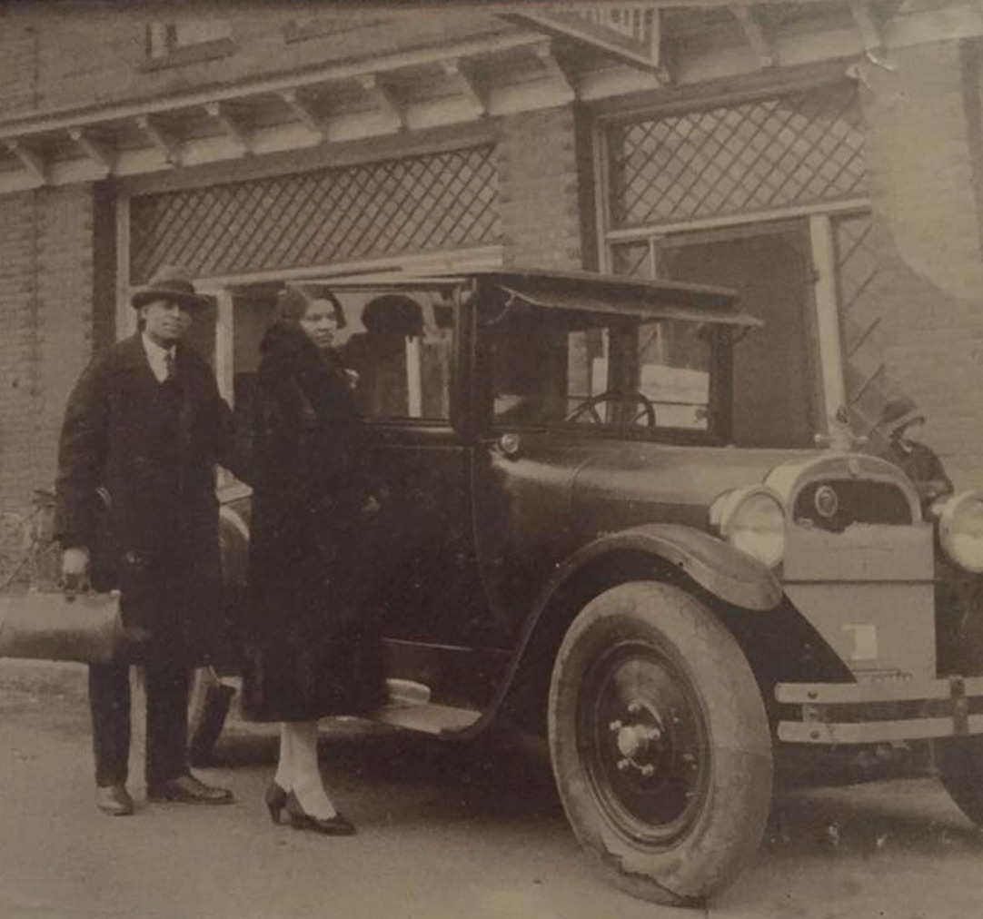 Nannie and John Kilby standing in front of a motor car and the Kilby Hotel in High Point, NC.