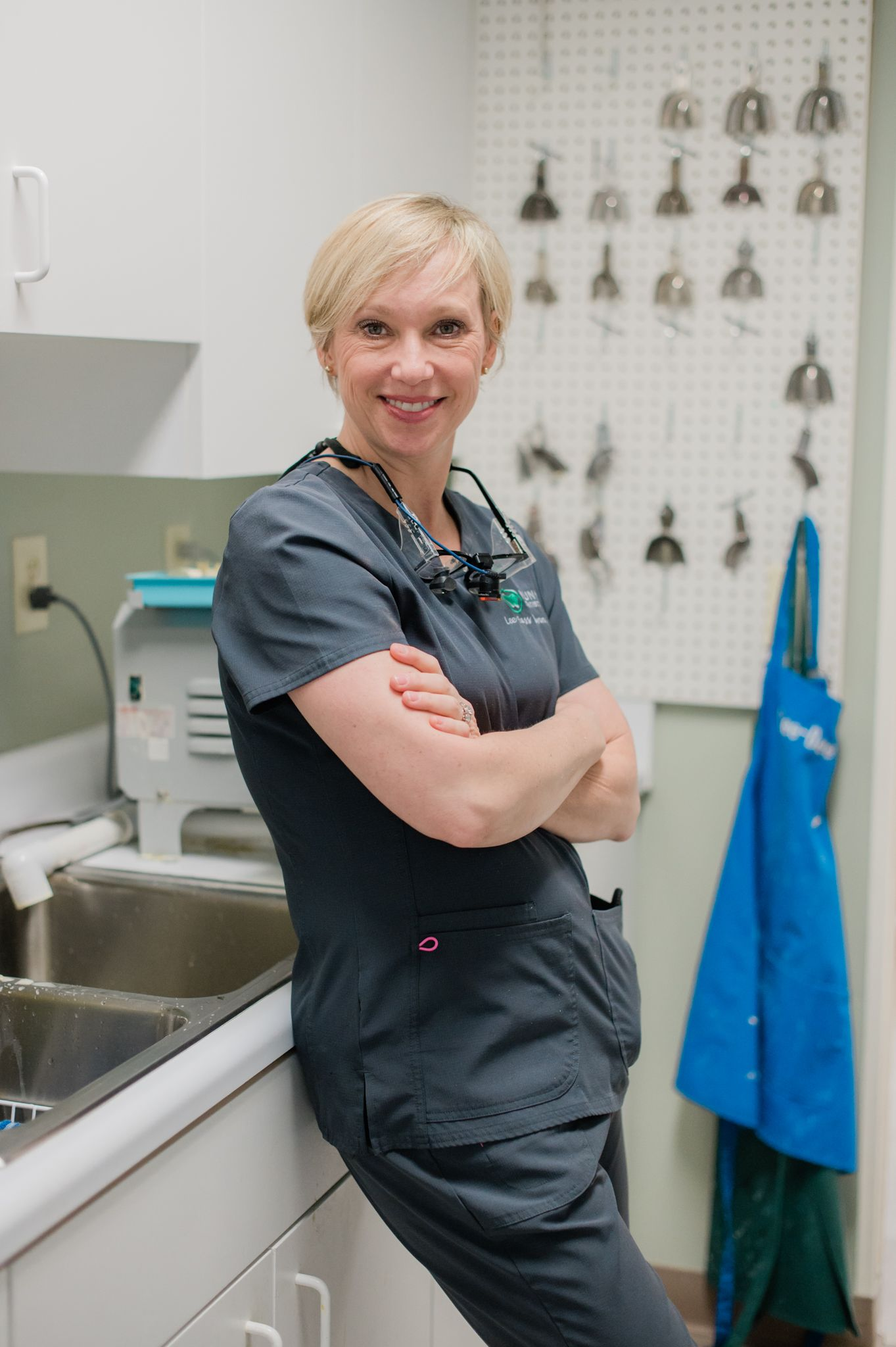 Dr. Lee Bass Nunn, dentist at Nunn Dentistry in High Point, NC wears scrubs and leans on the counter in her office.