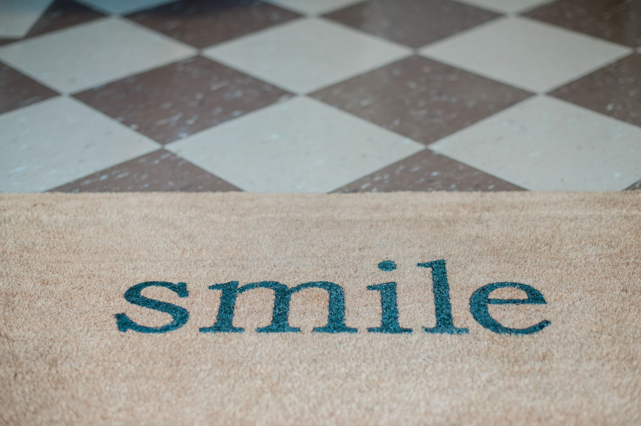 "A floor mat that says ""Smile"" in the doorway of Nunn Denistry in High Point, NC."