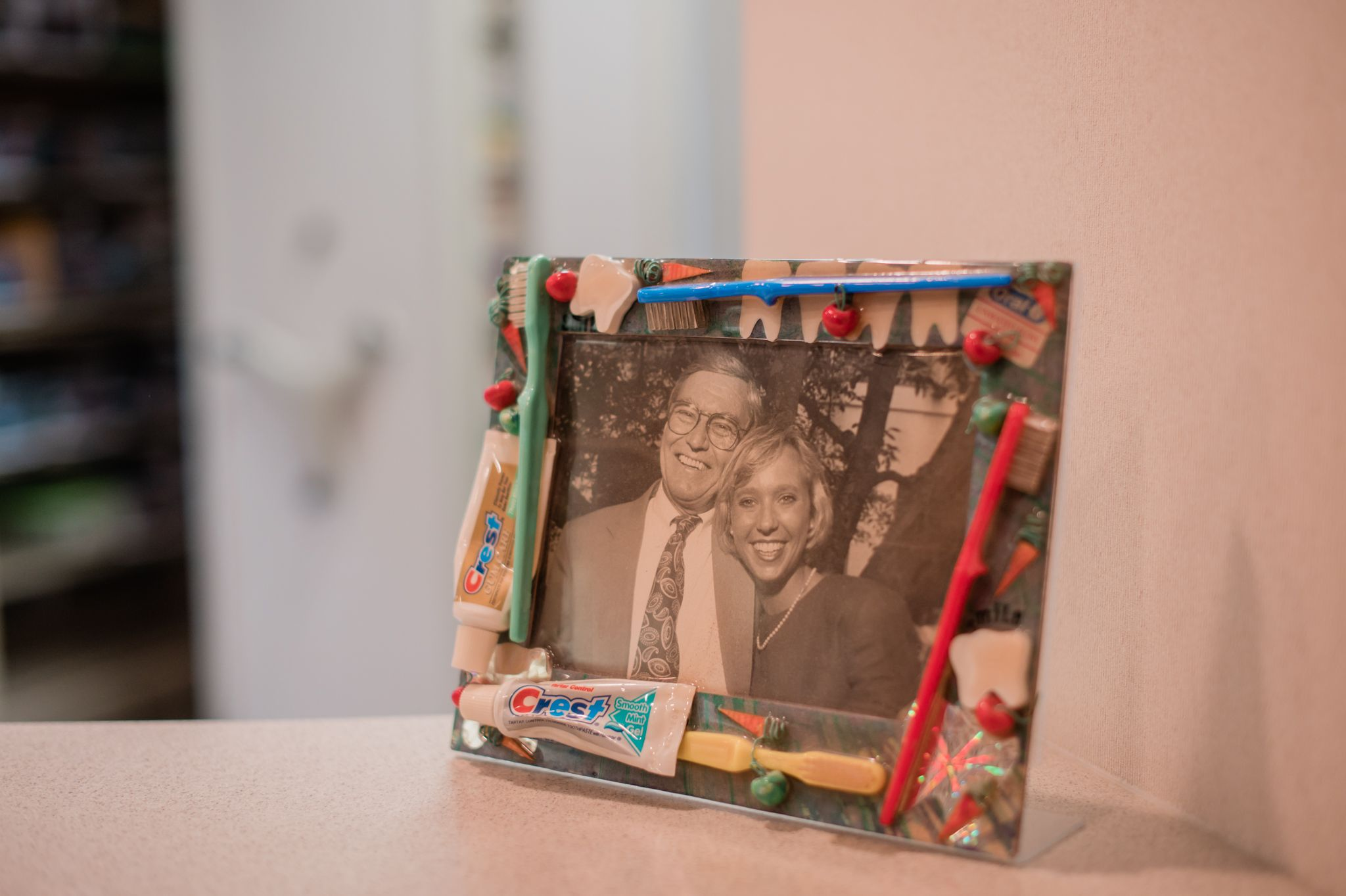 A photo in a frame with toothbrushes and toothpaste of Dr. Lee Bass Nunn with her father, Dr. Bass.