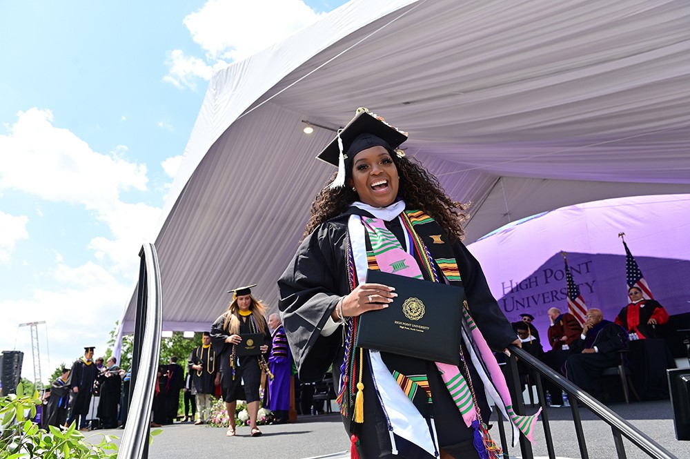 A woman accepts her diploma from High Point University at the 2021 High Point University Commencement.