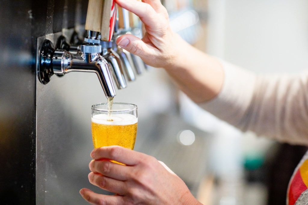 A woman pours a beer from the draft at Goofy Foot Taproom in High Point, NC.