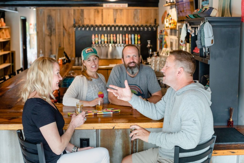 A couple sits at the bar at Goofy Foot Taproom in High Point, NC chatting with owners, Jeff and Tiffany Thompson.