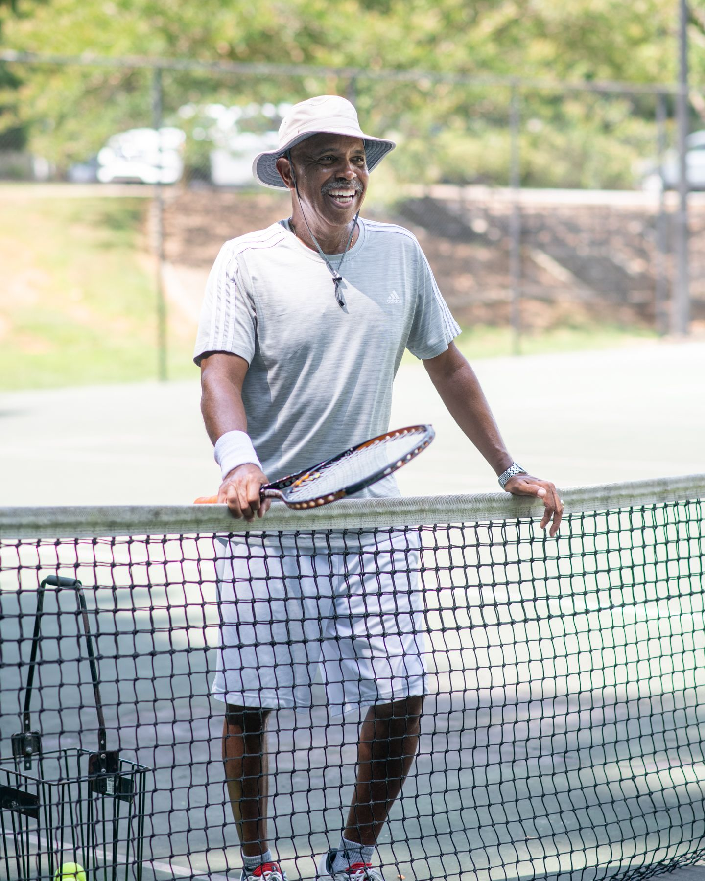 Junius Chatman, Tennis Director at the Oak Hollow Tennis Center in High Point, NC, laughs at the camera.