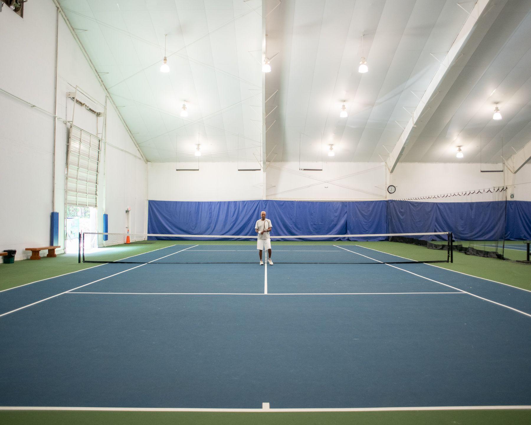 Junius Chatman, tennis director at Oak Hollow Tennis Center in High Point, NC, stands far away on indoor court.