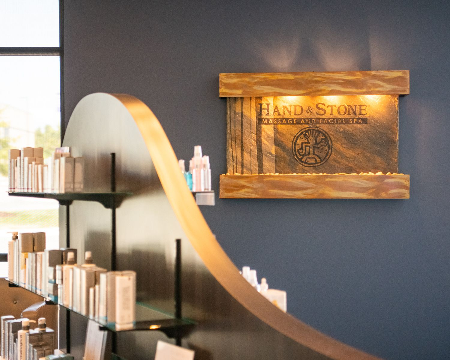 """A backlit sign that says """"Hand & Stone Massage & Facial Spa"""" in High Point, NC."""