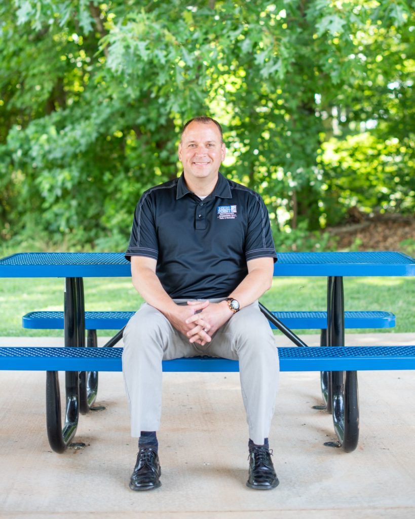 Lee Tillery, Director of High Point Parks & Rec, sits at a picnic table at the High Point Tennis Center.