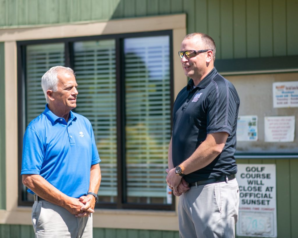 Lee Tillery stands chatting with Steve High, PGA Golf Administrator at Oak Hollow Golf Course.