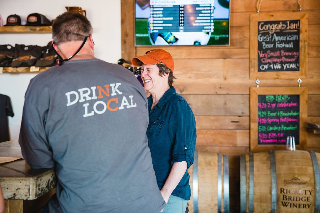 Two people laugh at Brown Truck Brewery in High Point, NC.